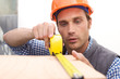 Laborer working with measuring tape