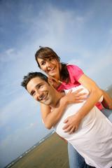 homme portant une femme souriante sur son dos à la mer