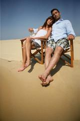 Homme et femme fermant les yeux assis en bord de plage