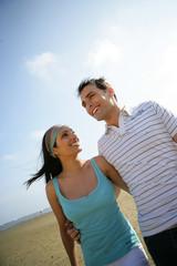 homme et femme souriants en se baladant à la plage