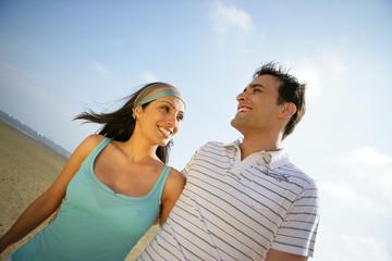 Jeune couple souriant en se baladant au bord de l'eau
