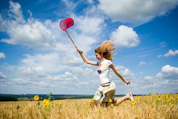 Young beautiful girl runs in wheat