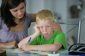 petit garçon faisant des devoirs près d'une femme