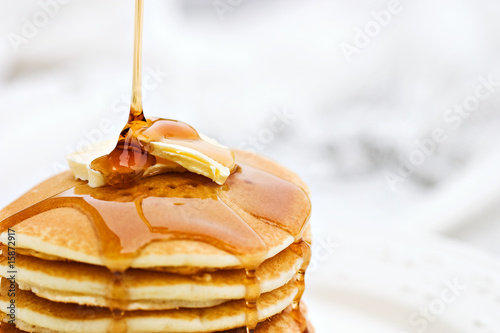 Maple syrup pouring onto pancakes. - 15872917