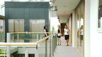 Businesswomen shaking hands and walking in a building