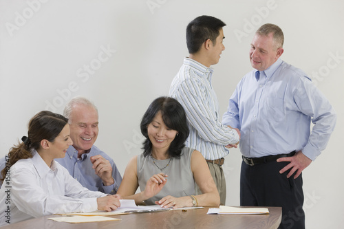 Meeting of five executives over paperwork.