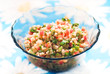 Tabouli middle eastern salad at glass bowl over floral napkin