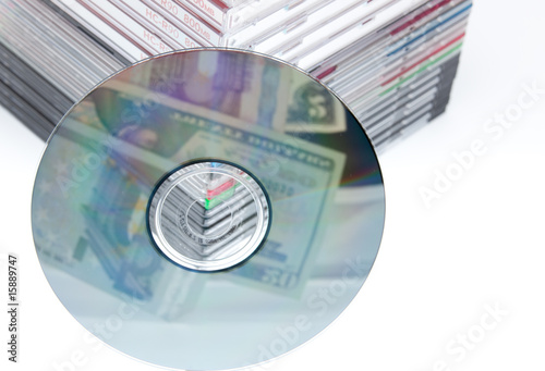 a blank dvd or cd with stack of empty cd cases on background