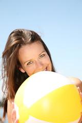 frau lächelt am strand mit wasserball