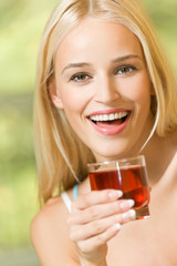 Happy young woman with glass of garnet juice