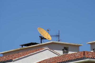 Antena parabolica amarilla en el tejado.