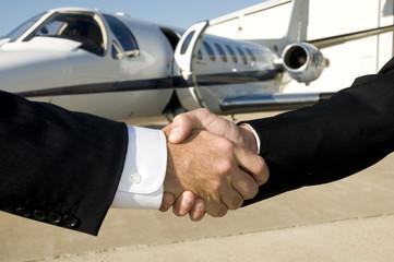 Businessmen shaking hands in front of corporate jet