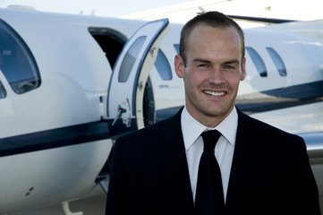 Businessman in front of corporate jet