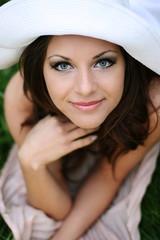 lächelndes Portrait einer schönen Frau mit weißem Hut
