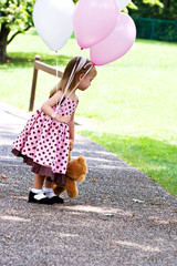 Little girl at a park with balloons and a little brown teddy.
