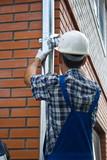 Man installing  rain gutter system poster