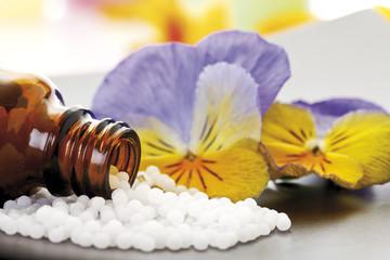 Medizin, Flasche mit Pillen vor Hornveilchen (Viola cornuta)