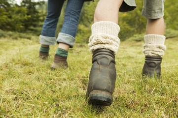 Zwei Personen zu Fuß unterwegs, laufen über Wiese