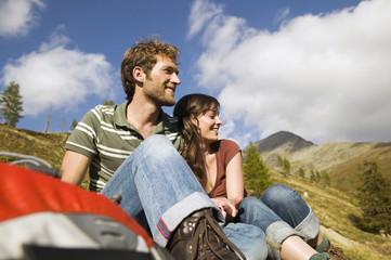 Junges Paar sitzt irgendwo in den Bergen