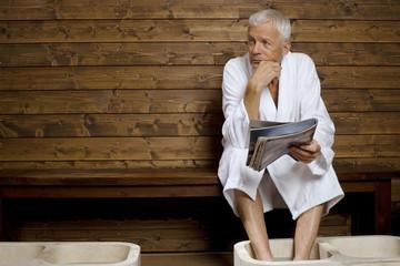Deutschland, älterer Mann beim Fußbad im Heilbad
