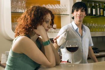 Junge Frau in der Bar mit einem Glas Wein
