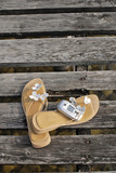 Italy, Lake Garda, Sandals and handy on wooden dock, close-up