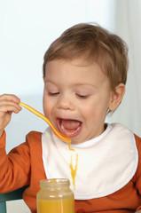 Kleines Kind isst Brei und schlabbert