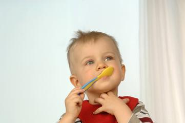 Kleiner Junge mit Löffel im Mund