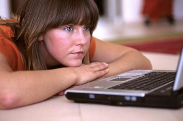 Junge Frau starrt auf Laptop, wartet