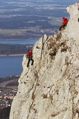 Deutschland, Bayern, zwei Menschen klettern an Felswand