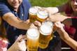 Deutschland, Bayern, Fröhliche Menschen prosten einander in Biergarten,