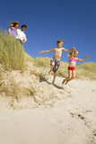 Germany, Baltic sea, Family in sand dunes, children jumping down sand dunes