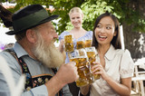 Germany, Bavaria, Upper Bavaria, Bavarian man and Asian woman in beer garden raising stein glasses, portrait