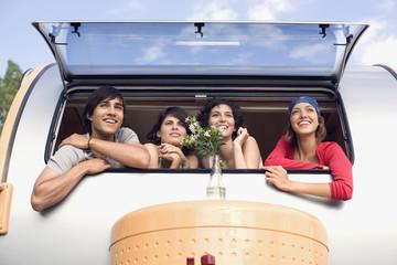 Junge Menschen schauen aus Campinganhänger, Camping