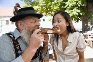Deutschland, Bayern, Bayer Mann und Frau essen Brezel, Portrait