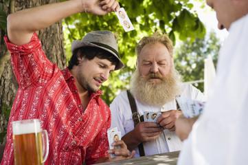 Deutschland, Bayern, Männer spielen Karten im Biergarten