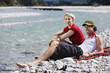 Germany, Bavaria, Tölzer Land, Young couple sitting on riverbank