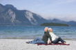 Germany, Bavaria, Senior couple relaxing on lakeshore, sitting back to back
