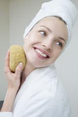 Frau jung reinigen Gesicht mit Schwamm