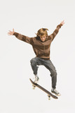 Teenage boy (13-14) performing jump on skateboard, arms out