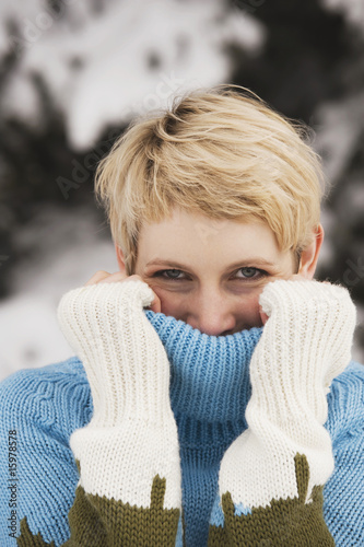 Italy, South Tyrol, Young woman, covering face with turtleneck pullover, portrait, close-up