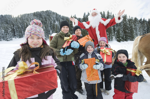 Italy, South Tyrol, Seiseralm, Children holding gift parcels, Santa Claus in background, portrait