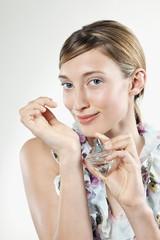 Frau jung auftragen Parfüm auf ihr Handgelenk, Portrait
