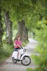 Deutschland, Bayern, Junger Mann auf Moped, Lächeln, Portrait