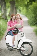 Deutschland, Bayern, Junges Paar mit Landkarte auf Motorroller