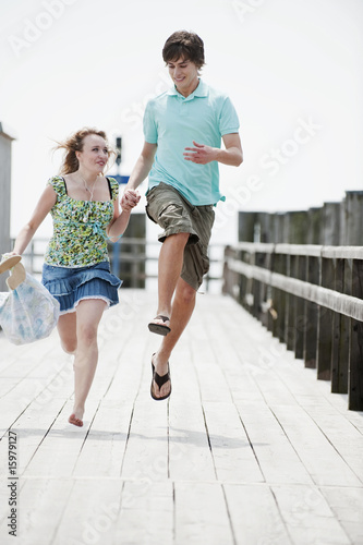 Germany, Bavaria, Ammersee, Young couple running on pier