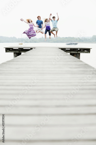 Germany, Bavaria, Ammersee, Four friends on jetty jumping in air