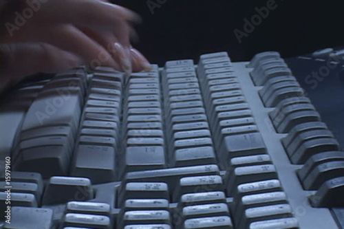 Woman types at computer keyboard