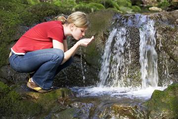 Frau jung trinken Wasser aus Bach