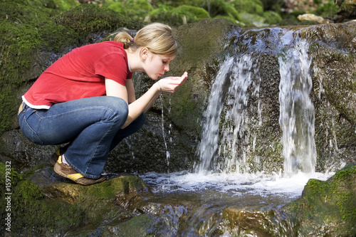 Young woman drinking water from stream, side view